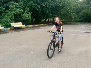 девушка учится кататься на велосипеде